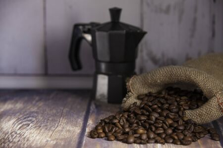 coffee beans coming out of a sack and italian coffee maker on wooden table