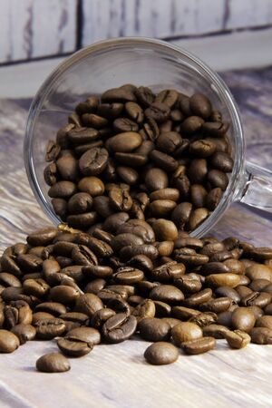 coffee beans coming out of a glass cup on a wooden table Stok Fotoğraf