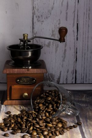 coffee beans coming out of a glass cup and a wood grinder with the word coffee the background on a wooden table Stok Fotoğraf