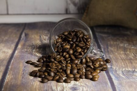 coffee beans coming out of a glass cup with a sack in the background on a wooden table