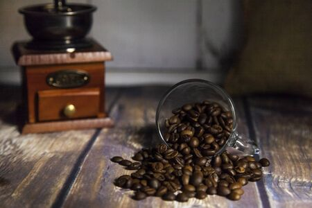 coffee beans coming out of a glass cup with a grinder and a sack in the background on a wooden table