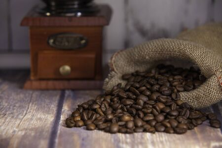 coffee beans coming out of a sack and grinder coffee on wooden table