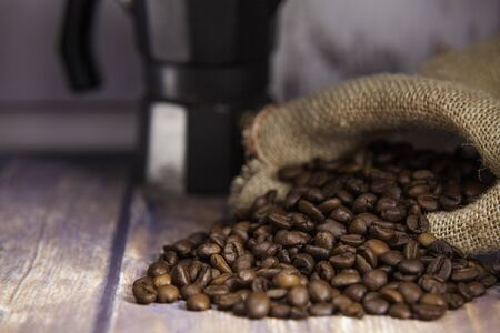 coffee beans coming out of a sack and italian coffee maker on wooden table close-up