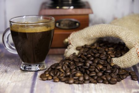 cup of coffee, coffee beans coming out of a sack and coffee grinder on wooden table