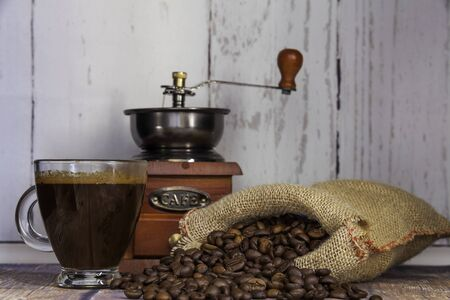 cup of coffee, coffee beans coming out of a sack and coffee grinder on wooden table on wooden background