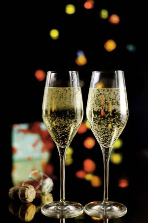Two champagne glasses, cork stopper, present and lights unfocused on black background Stock Photo