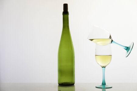 Two glasses of white wine in pirouette and green glass bottle on white