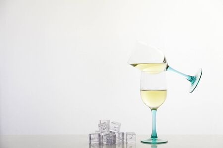 two glasses of white wine in pirouette and ice cubes on white background Reklamní fotografie