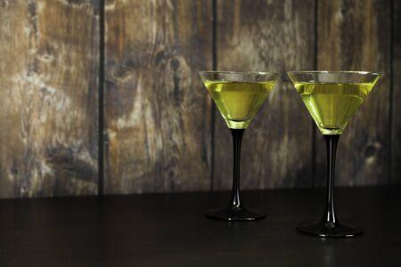 zwei gelbe Cocktailgläser auf altem Holzhintergrund