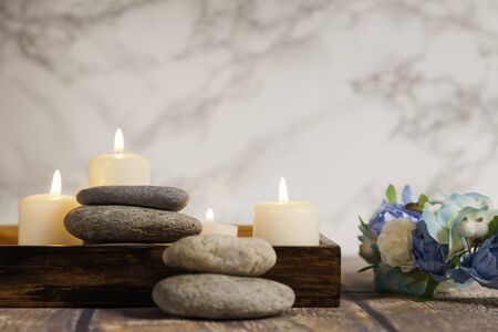 river pebbles and four lighted candles on wooden box on wood table with flowers and marble background