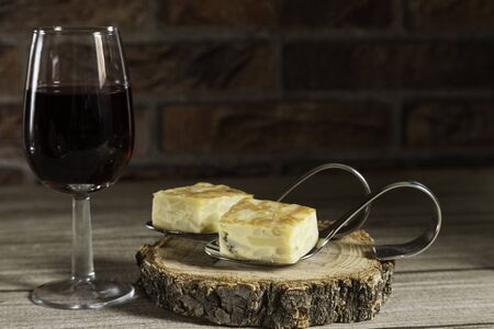 Spanish omelette brochettes on a wood slice and red wine glass on wooden table and red brick background