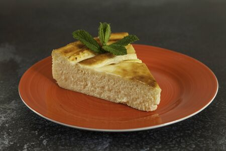 portion delicious cheesecake with mint leaf in a red plate on dark background marbling with copy space