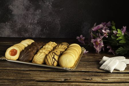 assorted tea pastes on a tray, tea bags and flowers on a wooden table and dark background