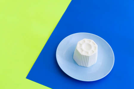 Typical Spanish fresh cheese in a blue plate on blue and yellow background Stok Fotoğraf