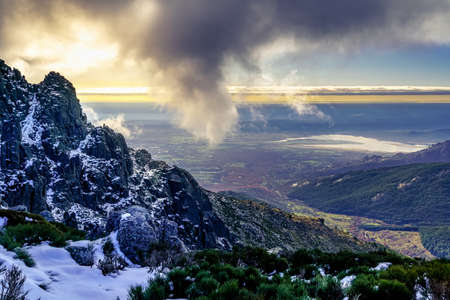 Snowy landscape on the rocky mountains of Madrid, dark clouds beginning to cover the sky and the sun setting on the horizon. Spain. 版權商用圖片