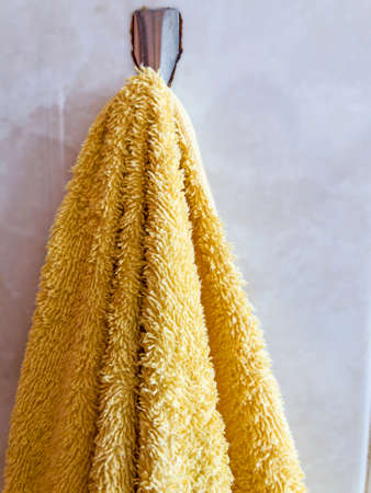 Yellow bath towel hanging on white background
