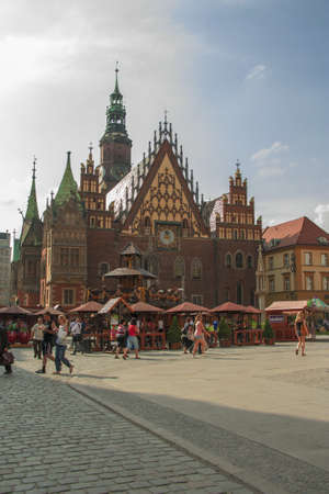City Hall in Wroclaw in Poland, historical building, with trade in the street in front, with men, women, children, shopping