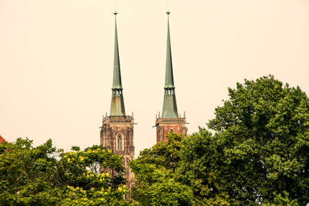 the two towers of the Cathedral of St. John the Baptist, in wroclaw in Poland, hidden brings the trees