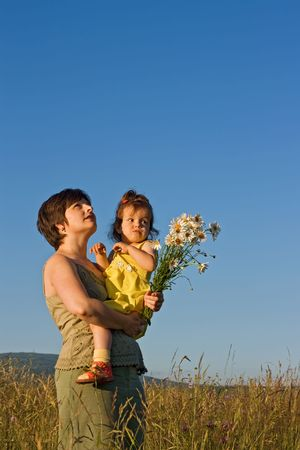Mother and her girl walking on the meadow in  summer day