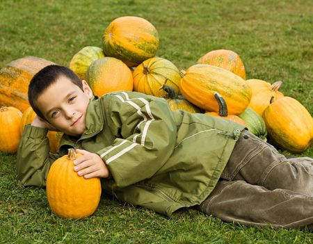 Boy lying and lean on his elbow in front of pumpkins