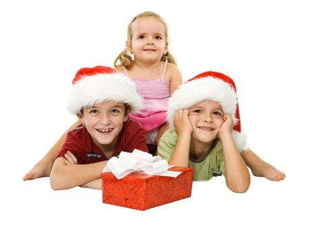 Three children laying on the floor in santa hats and smiling happy at christmas time Stock Photo