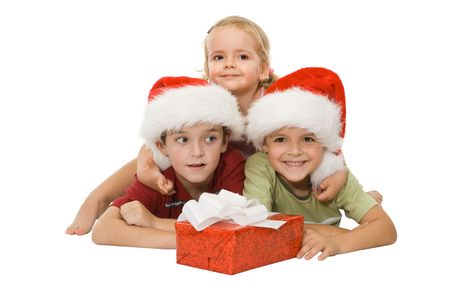 Three children laying on the floor in santa hats smiling and hugging happy at christmas time Stock Photo