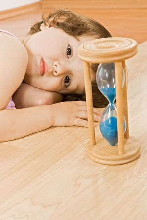 Little girl laying near a hourglass with blue sand  photo