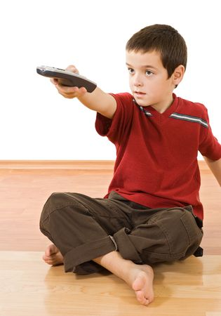 Little boy with a remote control sitting on the floor and watching tv