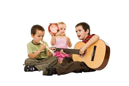 Three children sitting on the floor and playing with musical instruments