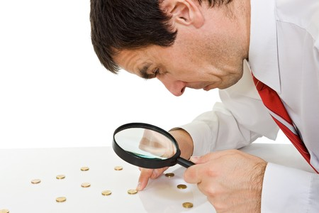 Businessman looking to the coins through a magnifying glass Stock Photo