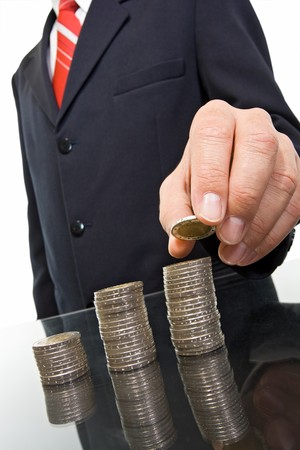 Businessman putting the coins in columns  Stock Photo