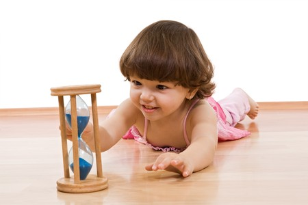 Little girl looking at a hourglass with blue sand