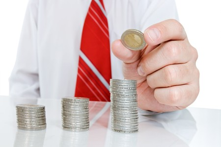 Businessman making columns from coins
