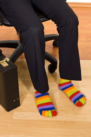 Businessman sitting in armchair and wearing unusual colorful socks