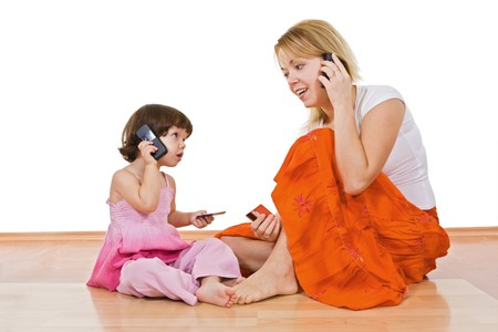 Young beautiful woman talking on the phone and holding in her hand a banking card and the little girl imitate her
