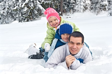 Happy family lying in snow, focus on the rear child