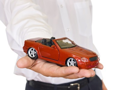 Businessman offering a car while keep a red toy car in one hand - isolated Stock Photo