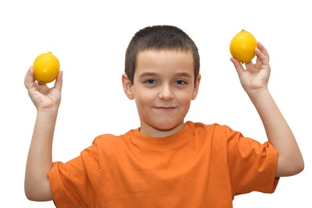 Boy holding in his hand two lemons -isolated Stock Photo