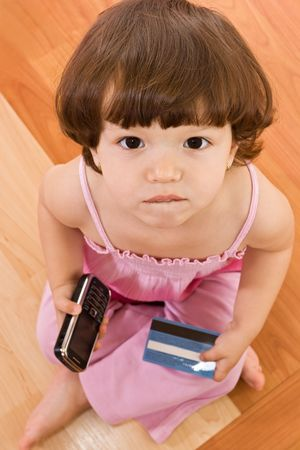 Little girl holding in her hands a mobile phone and a banking card Stock Photo