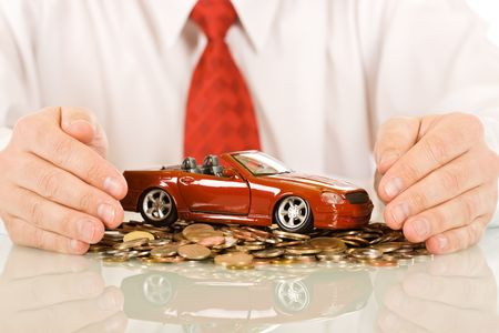 Businessman protecting a red toy car which is on a pile of coin