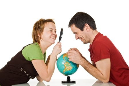 Happy couple looking at globe through a magnifying glass - isolated photo