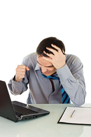 Angry businessman shows his frustration while working on the laptop - isolated