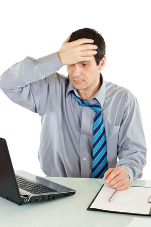 Shocked businessman looking at laptop and holding his head - isolated