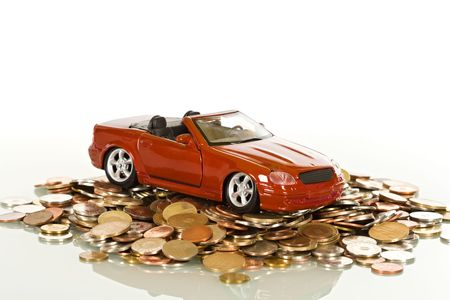Red toy car on a pile of coins, buying car concept