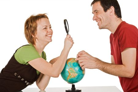 Happy couple looking to each other through a magnifying glass - isolated photo