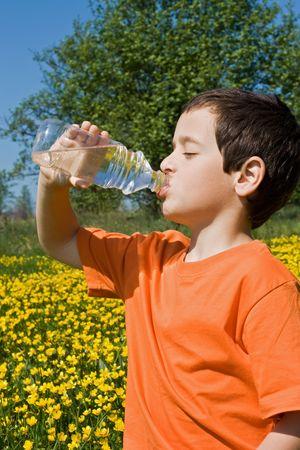 Boy drinking water from bottle photo