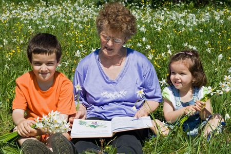 Grandmother reading to her happy grandchildren a tale  Stock Photo