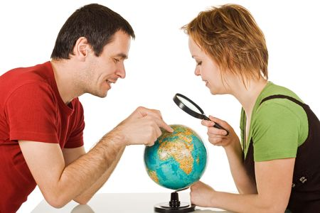 Happy couple looking at globe through a magnifying glass - isolated Stock Photo