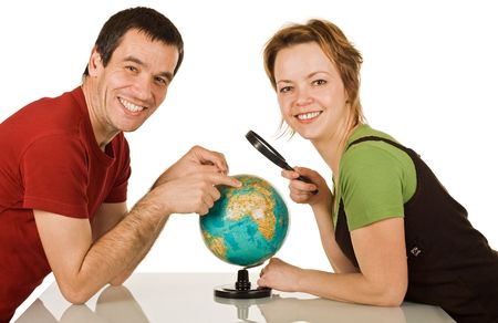 Happy couple with globe looking to the camera - isolated photo