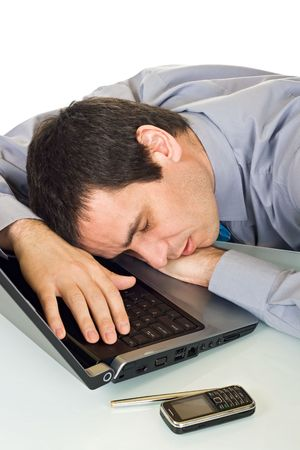 Tired businessman sleeping in the office, he putting his head onto keyboard of the laptop - isolated